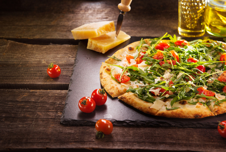 Pizza Caprese with arugula, cheese, yoghurt and cherry tomatoes closeup Banque d'images