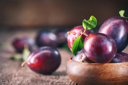 Plum. Juicy ripe organic plums closeup, over wooden background Foto de archivo