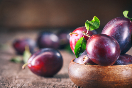 Plum. Juicy ripe organic plums closeup, over wooden background Stock Photo