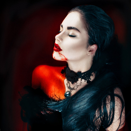 Beauty Halloween sexy vampire woman with dripping blood on her mouth 스톡 콘텐츠