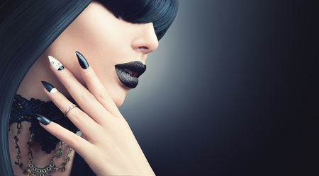 Fashion Halloween model girl with trendy gothic black hairstyle, makeup and manicure