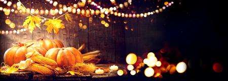 感謝祭の日の背景。カボチャやトウモロコシの穂軸で飾られた木製のテーブル