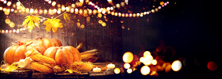 Thanksgiving Day background. Wooden table decorated with pumpkins and corncobs