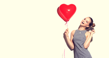 Beauty joyful teenage girl with red heart shaped air balloon