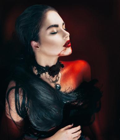 Schoonheid Halloween sexy vampier vrouw met druipend bloed op haar mond