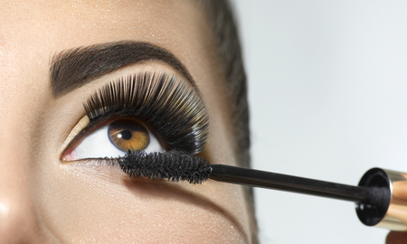 Long lashes closeup. Beautiful woman applying mascara on her eyes. Makeup Banque d'images