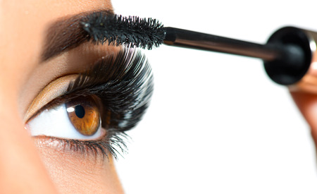 Long lashes closeup. Beautiful woman applying mascara on her eyes. Makeup Banco de Imagens