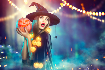 Halloween. Witch with a carved pumpkin and magic lights in a dark forest 스톡 콘텐츠
