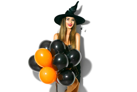 Halloween party girl. Sexy witch holding black and orange air balloons. Beautiful young woman in witches hat and costume Reklamní fotografie