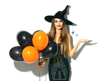 Halloween-feestmeisje. Sexy heks die zwarte en oranje luchtballons houdt. Mooie jonge vrouw in heksenhoed en kostuum Stockfoto