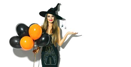 Chica de fiesta de Halloween. Bruja atractiva que sostiene los globos de aire negros y anaranjados. Hermosa mujer joven en sombrero y traje de brujas Foto de archivo - 86272562