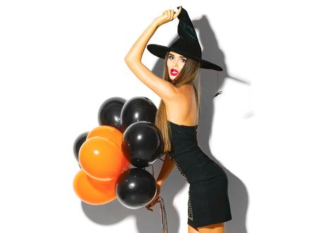 Halloween feestmeisje. Sexy heks met zwarte en oranje luchtballonnen. Mooie jonge vrouw in heksen hoed en kostuum