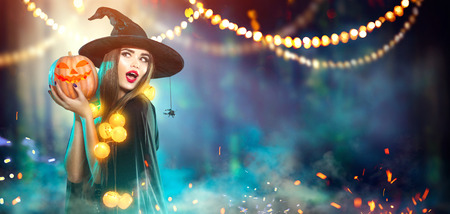 Halloween. Witch with a carved pumpkin and magic lights in a dark forest Archivio Fotografico