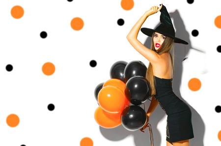 ハロウィーン パーティー ガール。黒とオレンジ色の気球を持ってセクシーな魔女。魔女帽子と衣装の美しい若い女性