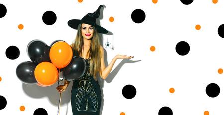 Chica de fiesta de Halloween. Bruja atractiva que sostiene los globos de aire negros y anaranjados. Hermosa mujer joven en sombrero y traje de brujas Foto de archivo - 86272571