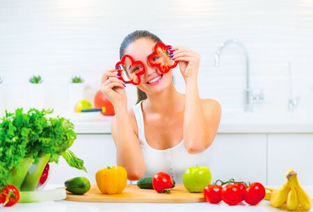 Beauty young funny woman holding fresh vegetables and smiling in her kitchen at home. Healthy eating concept