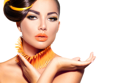 Fashion model girl with yellow and orange makeup. Creative hairstyle