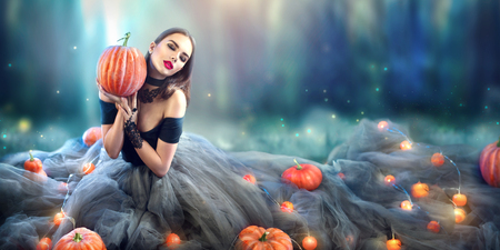 Halloween witch with a carved pumpkin and magic lights in a dark forest Stockfoto