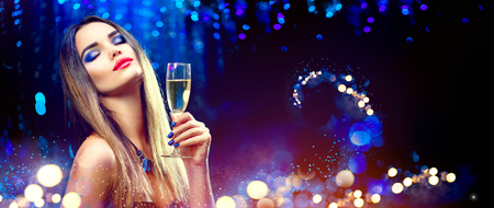 Sexy model girl drinking champagne over holiday glowing background Foto de archivo