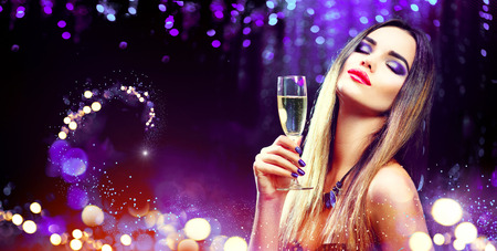 Sexy model girl drinking champagne over holiday glowing background Standard-Bild