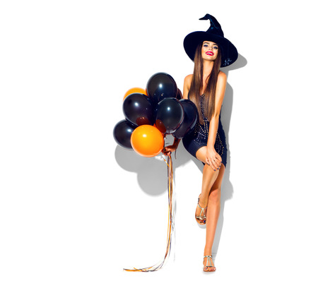 Halloween party girl. Sexy witch holding black and orange air balloons. Beautiful young woman in witches hat and costume Archivio Fotografico