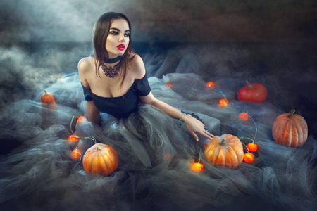 Sexy Halloween witch with pumpkins and magic lights