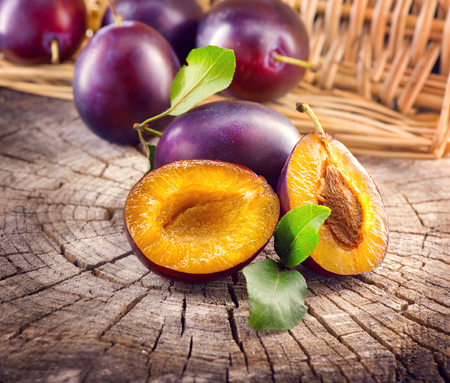 Plum. Juicy ripe organic plums closeup, over wooden background Stock Photo