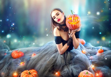 Sexy Halloween-heks met gebogen pompoenen en magische lichten