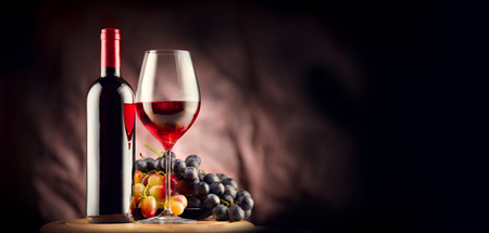 Wine. Bottle and glass of red wine with ripe grapes still life