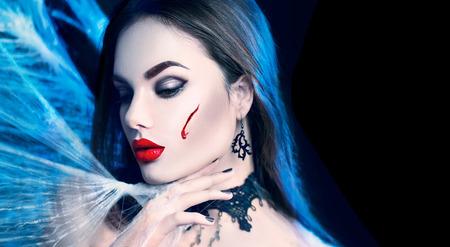 Víspera de Todos los Santos. Belleza sexy mujer vampiro posando en la oscuridad, el uso de la tela de araña