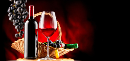 Wine. Bottle and glass of red wine with ripe grapes over black background Фото со стока