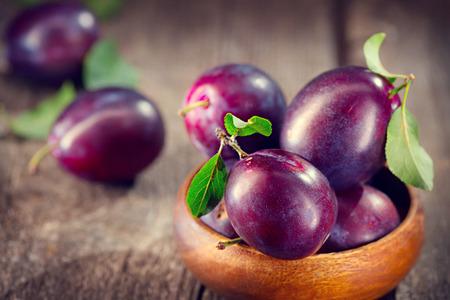 Plum. Juicy ripe organic plums closeup, over wooden background Banco de Imagens