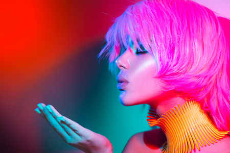 Fashion model woman in colorful bright lights with trendy make-up, manicure and haircut