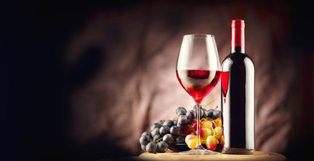Wine. Bottle and glass of red wine with ripe grapes over black background Standard-Bild