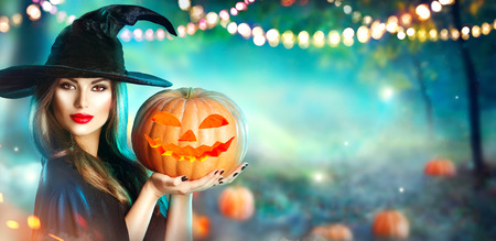 Halloween witch with a carved pumpkin and magic lights in a dark forest Reklamní fotografie