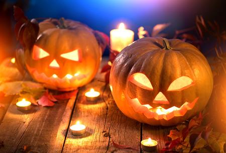 tallado en madera: Linterna del enchufe de cabeza de calabaza de Halloween con velas ardientes sobre fondo de madera Foto de archivo