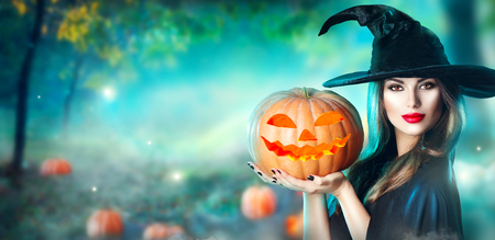 Halloween witch with a carved pumpkin and magic lights in a dark forest Standard-Bild