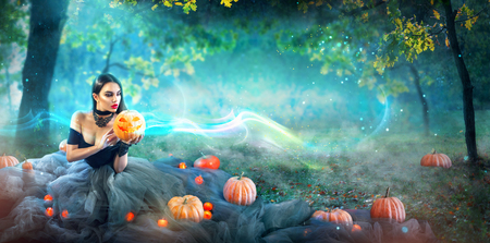 Halloween witch with a carved pumpkin and magic lights in a dark forest Archivio Fotografico