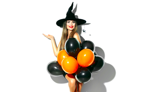 Halloween. Sexy witch holding black and orange air balloons