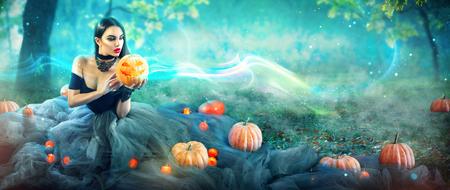 Halloween heks met een gesneden pompoen en magische lichten in een donker bos