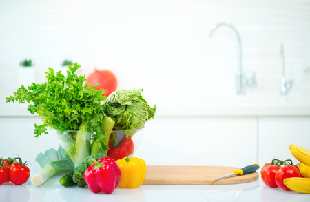 Kitchen table with fresh organic vegetables and fruits. Healthy eating concept