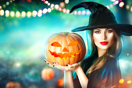 Halloween witch with a carved pumpkin and magic lights in a dark forest Фото со стока