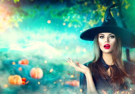Halloween witch pointing hand over dark magic field with pumpkins and magic lights in forest Stockfoto