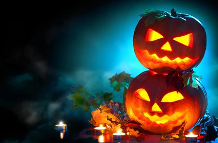Fond de vacances de Halloween. Citrouilles d'Halloween courbées avec des bougies allumées