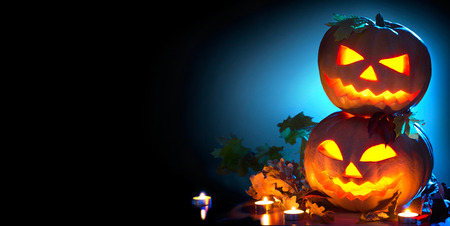Halloween holiday background. Curved Halloween pumpkins with burning candles