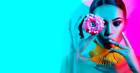 Fashion model woman posing in studio with donut in colorful bright lights Stock Photo