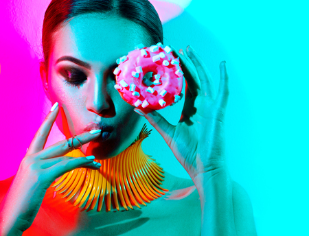 smoky eyes: Fashion model woman posing in studio with donut in colorful bright lights Stock Photo