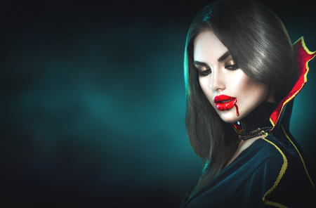 Halloween. Sexy vampire woman with dripping blood on her lips 스톡 콘텐츠
