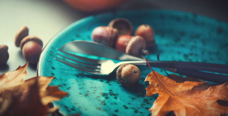 感謝祭の休日テーブルを提供しています。明るい秋の葉で飾られた木製のテーブル