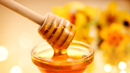 Thick honey dripping from wooden stick over yellow background